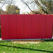 Red protective outdoor fence padding at Chicago Fire Academy soccer training facility.