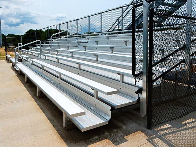 8 row bleachers with 4' aisle and black vinyl fenceguard at oconomowoc high school.