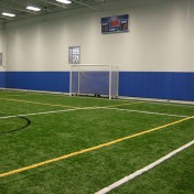 Wheeled soccer goal at indoor athletic facility.