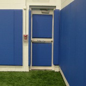 Custom wall padding on door and walls for indoor athletic facility.