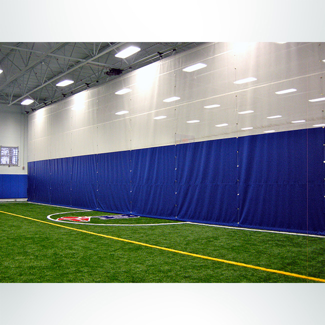 Fold-up motorized divider curtain for indoor soccer field. Royal blue vinyl and white mesh.