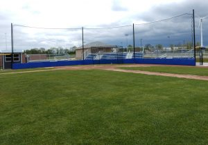 Custom blue wall padding with back-up netting in front of bleachers.