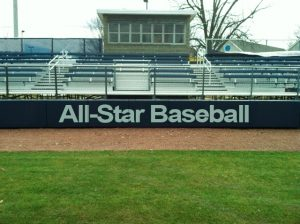 Outfield baseball pad with custom logo in front of bleachers.