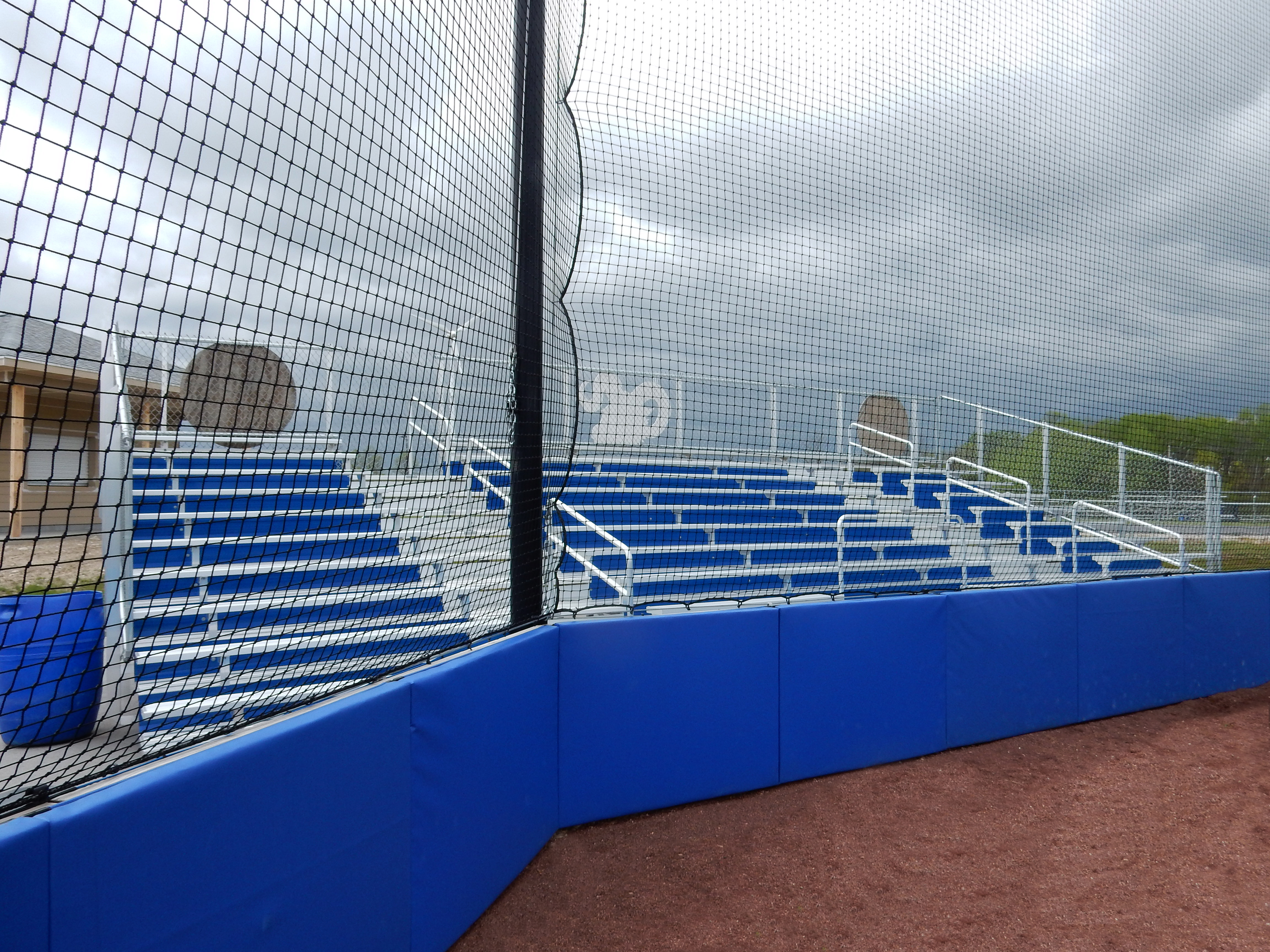 CustomPadding Protective padding for wall below net at a baseball stadium in front of the bleachers. Royal blue.