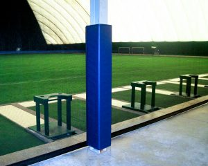 Four sided padding on metal beam at indoor soccer facility.