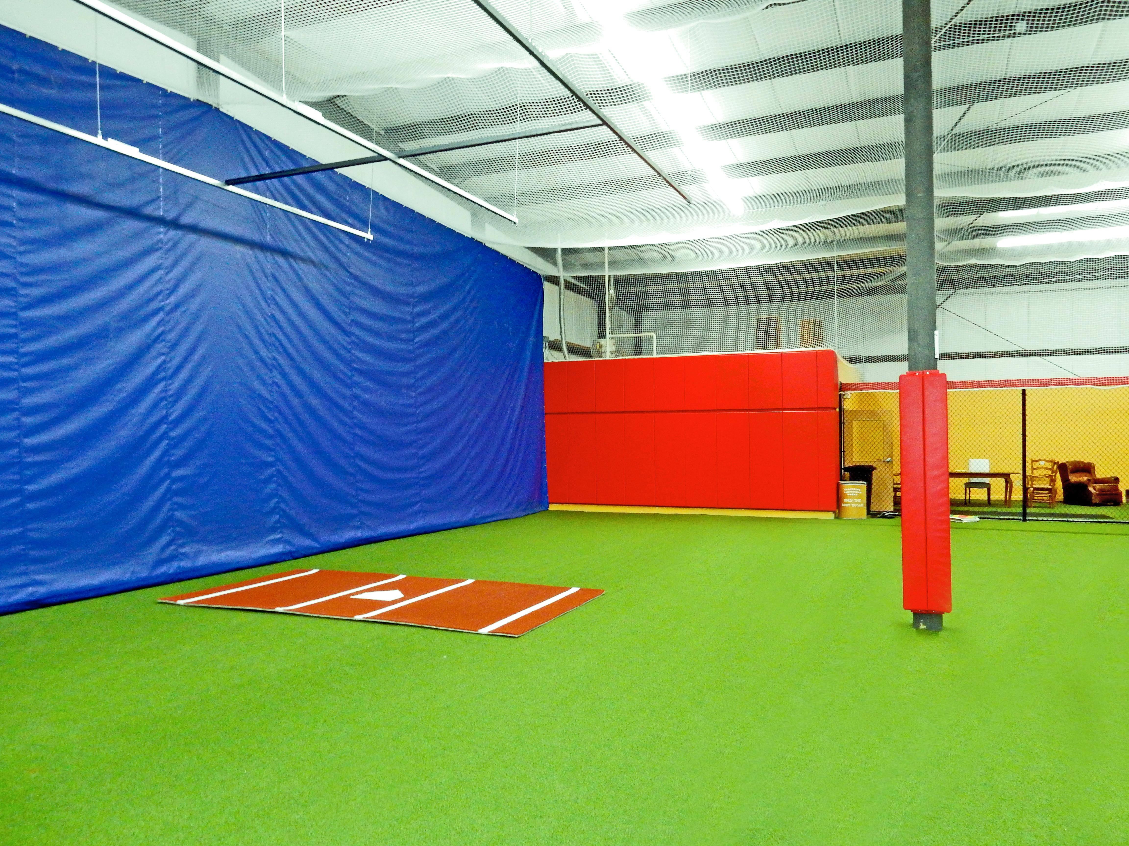 Red padding for wall at indoor baseball facility.