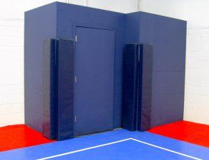 Blue protective padding for futsal field doors.
