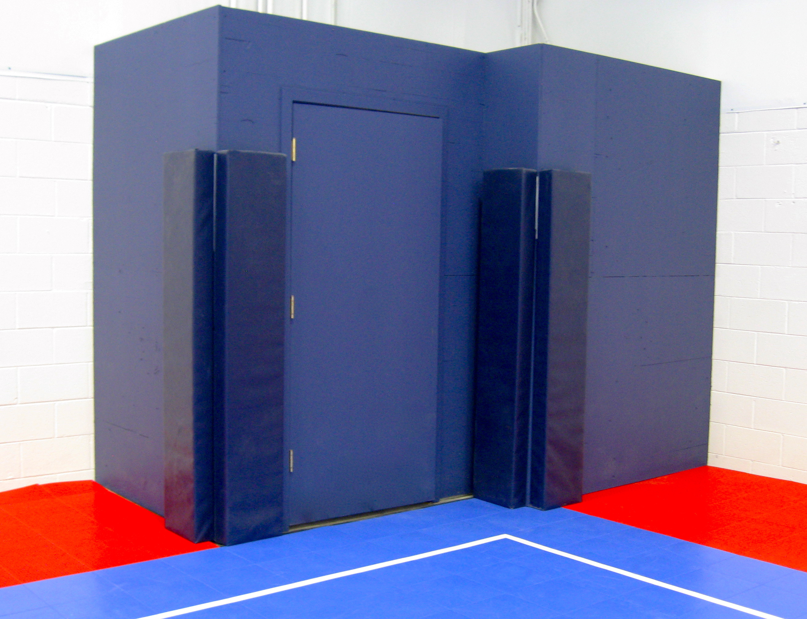 Blue protective padding for futsal field doors.