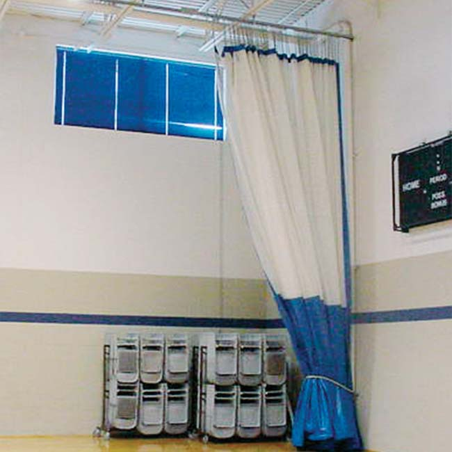 Walk-draw gym divider curtain retracted in white mesh and blue vinyl.