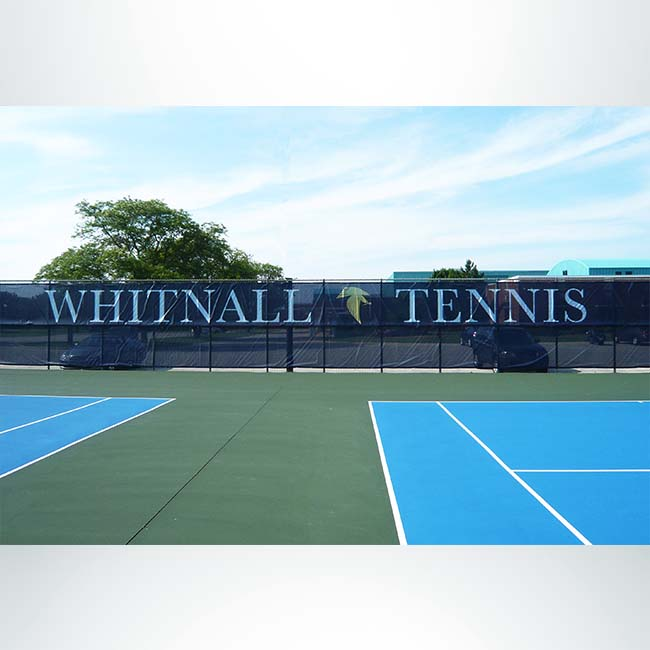 Windscreen on tennis court with custom logo.