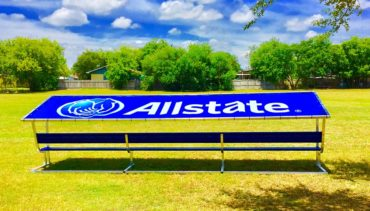 Covered athletic team bench with blue vinyl cover with all-state logo.