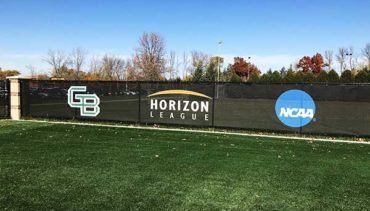 Custom windscreen for soccer stadium with school, conference and NCAA logos.