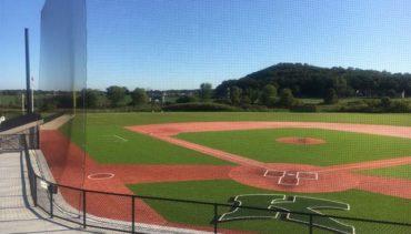 Custom engineered tieback baseball netting at a high school baseball stadium.