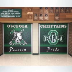 School branding door wrap with green, black, and white logo and graphics on high school gym doors.