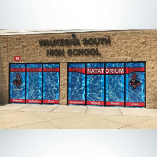 Entrance to school shown after school branding combination perforated window film and door wrap is installed.