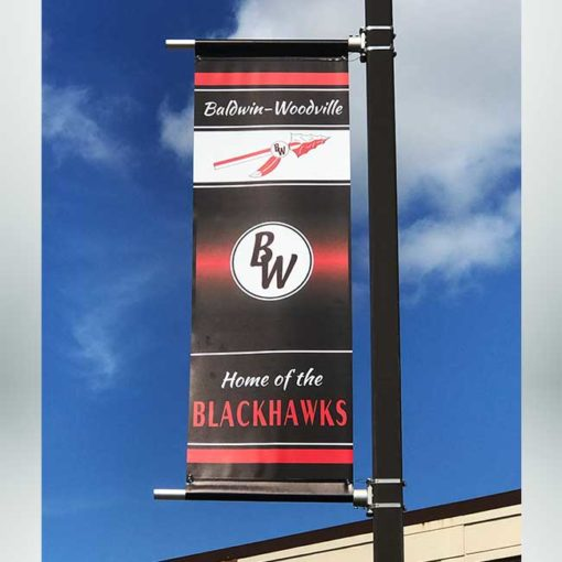 Light pole banner for athletic facility with black, red and white graphics.