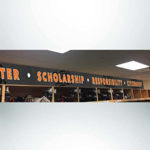 Locker room banding above lockers with character building words in black, orange and white.