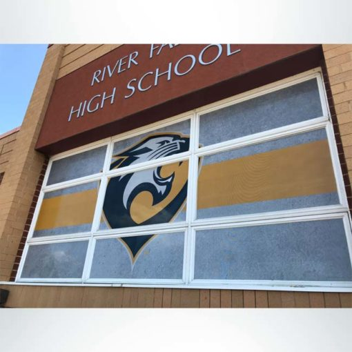 Perforated window film at front entrance of school. Black, white and yellow with logo.