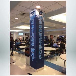 Concrete pillar wraps in blue, red and white with school logo.