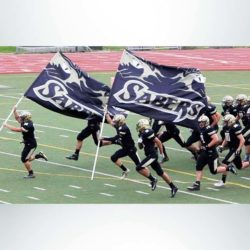 Spirit flag with navy blue and white graphic and the word Sabers carried by a football team.