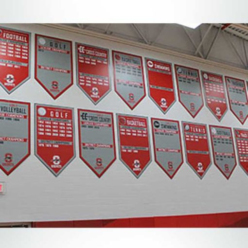 Vinyl gym banners with boys' sport championships in red and girls' sport championships in gray hanging on gym wall.