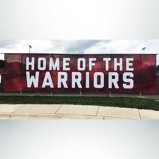 Windmesh with red and white graphic on fence at high school football stadium.