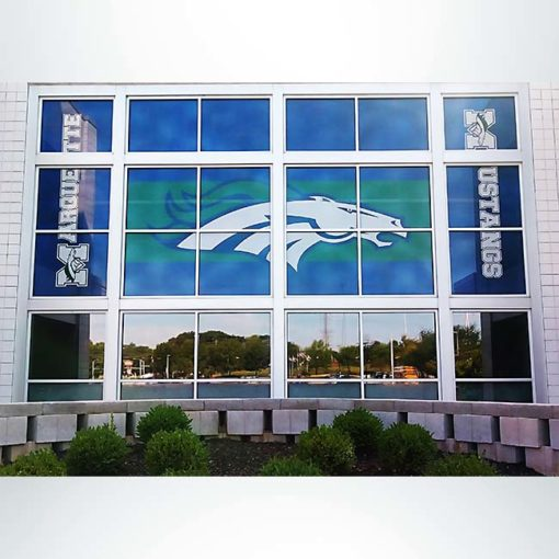 Window perf/see through film with blue, green and white graphics on windows at front entrance of school after branding.