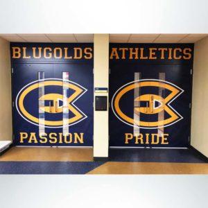 School branding custom door wrap with overhead wall graphic leading into gym.