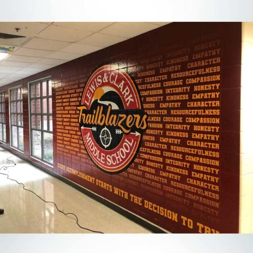 Wall wrap displaying core values in athletic hallway.