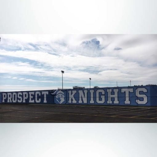 Windmesh on stadium fence with blue and white graphics.