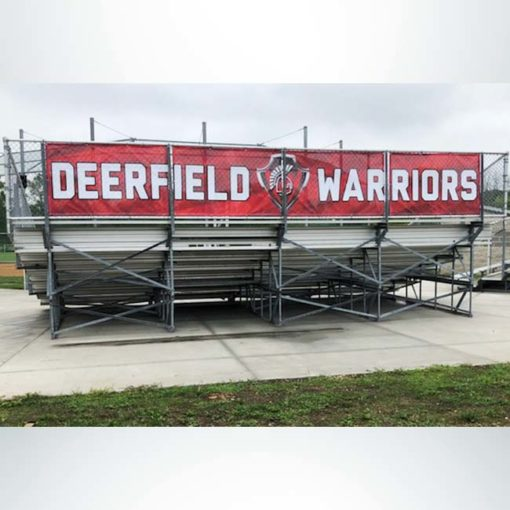 Windmesh on back of bleachers. Red and white graphics.