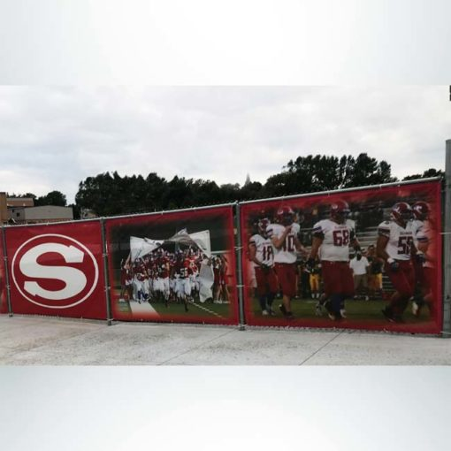 Windmesh for fencing at school stadium. Red and white logos and pictures.