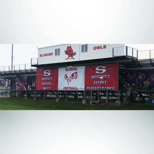 Windmesh on school stadium. Red and white logos and pictures.