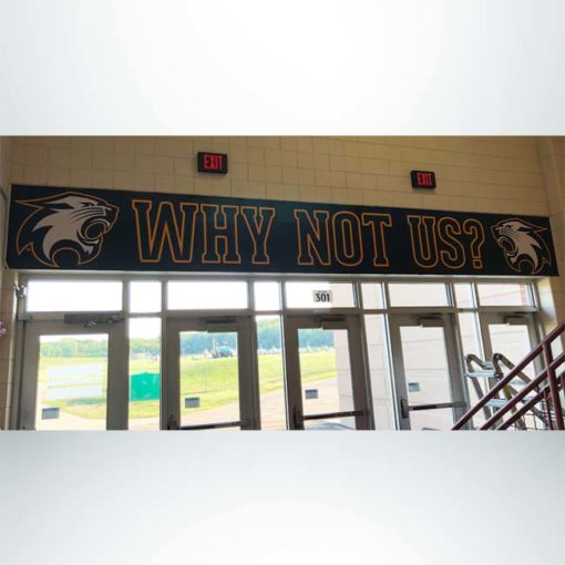 Wall wrap above school door in with blue and gold graphics.