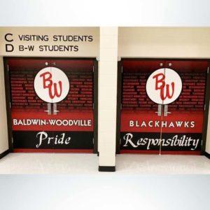 Vinyl double door wrap on school doors in red and black with school logo and character words.