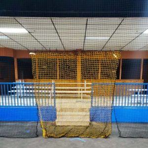 Barrier netting for an indoor futsal facility with a yellow net for a doorway.