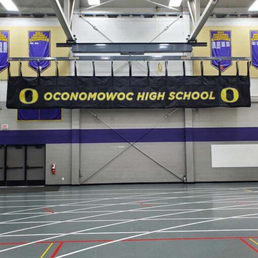 Branded mat hoist in high school gym.