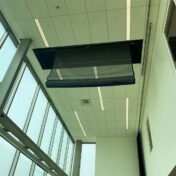 Motorized curtain divider stored in the ceiling.