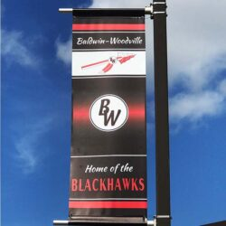 School Branding. Light pole banner in black white and red for athletic facility.