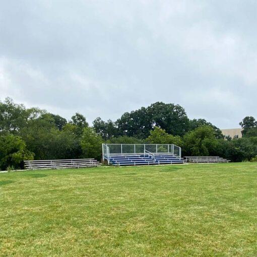 Model #B5R31A1GR. 5 row 31' bleachers with blue risers at a soccer field.