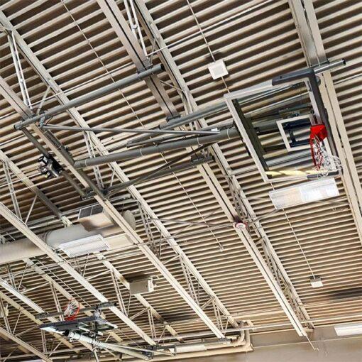 Ceiling mount basketball hoop in high school gymnasium.