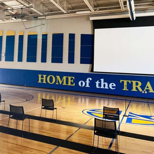 Wall padding with custom logo in gymnasium at Cristo Rey High School.