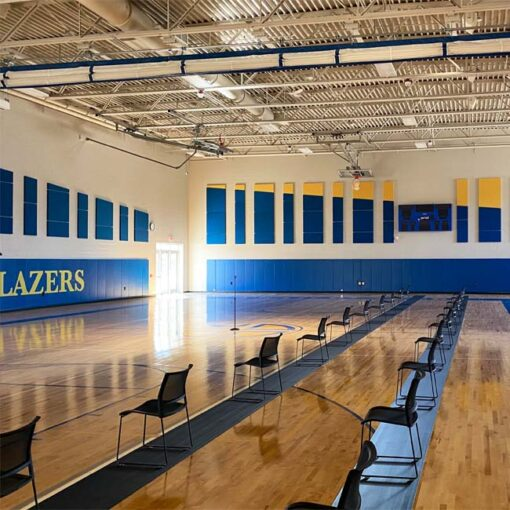 Wall padding. Motorized divider curtain. Ceiling-mount basketball hoops at Cristo Rey High School.