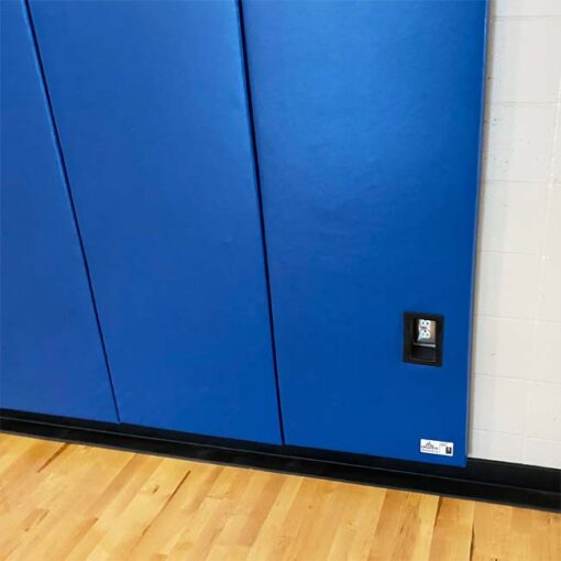 Wall padding in gymnasium with outlet cutout.