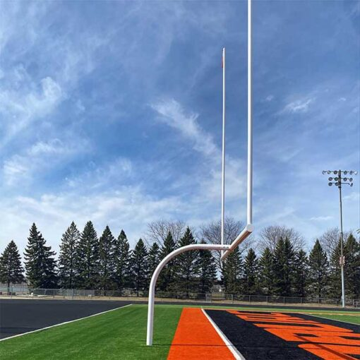 Football goal posts powder coated white at high school football field.