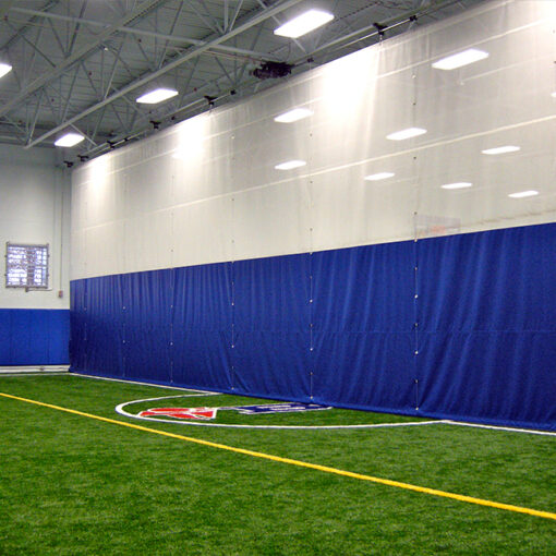 Divider curtain in custom blue and white. Custom fold up curtain to separate indoor soccer fieldw.